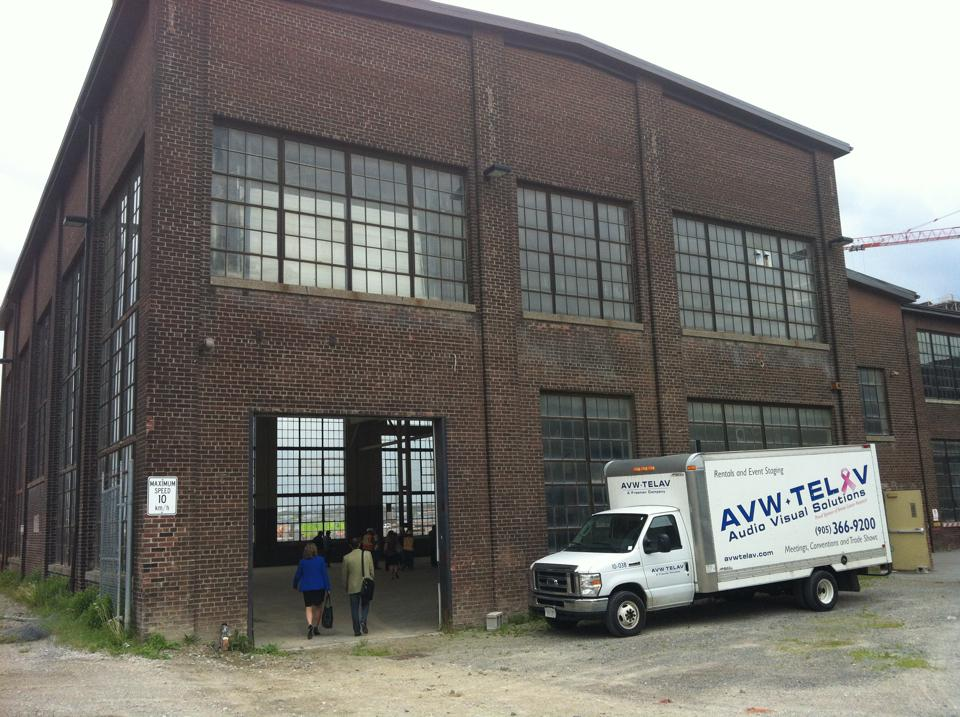 People entering a 2013 exhibition of plans for the Pan Am games; this is the north entrance door of the machine shop