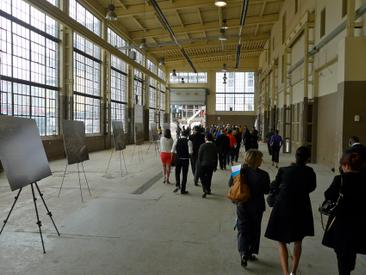 People strolling through the warehouse building during the 2013 exhibition showing plans for the area in anticipation of the Pan Am games.