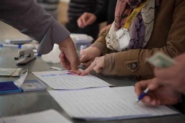 Woman giving thumbprint signature to claim the cash (Photo: Stella Chetham)